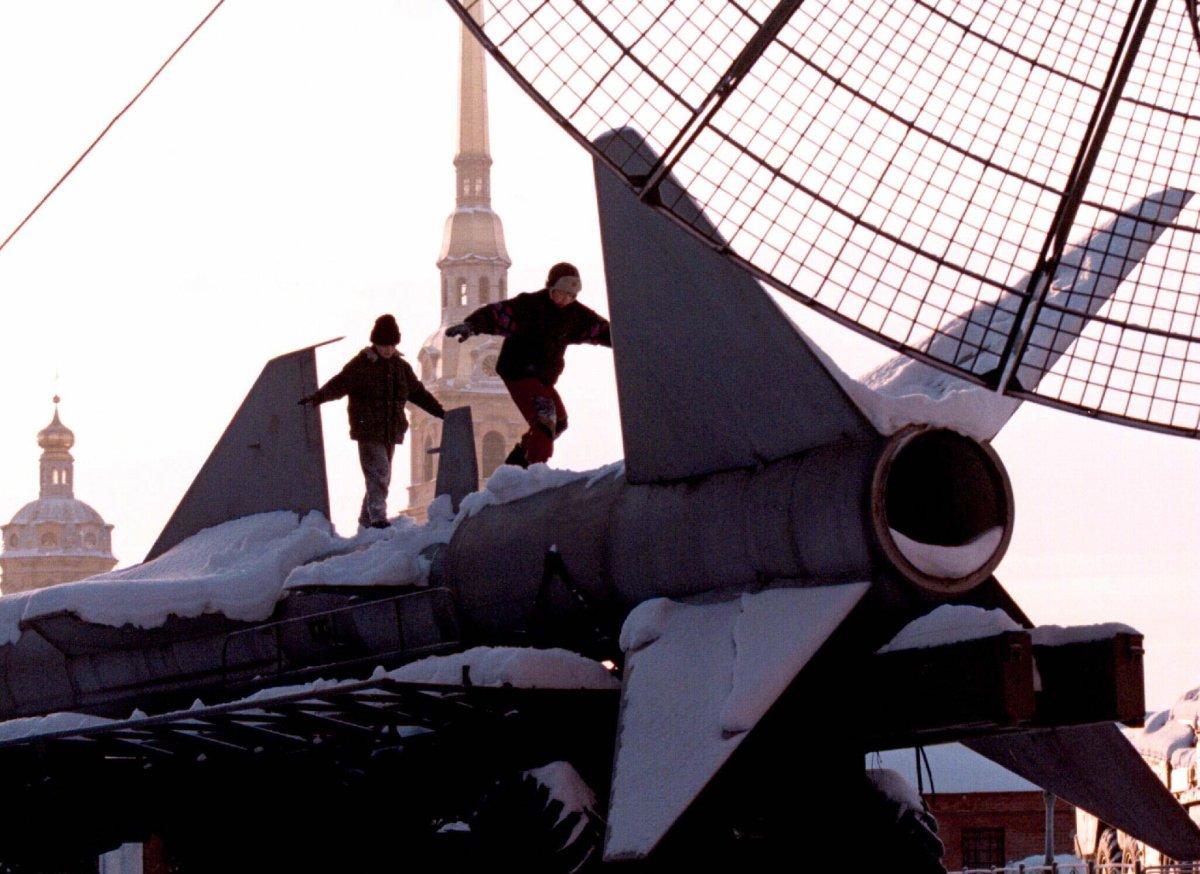 Дети играют на ракете класса «земля — воздух» на открытой выставке музея в Санкт-Петербурге, январь