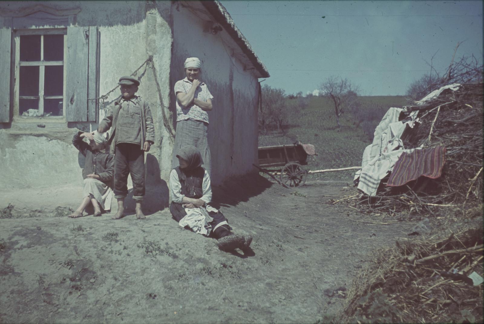 Три поколения крестьянской семьи перед домом
