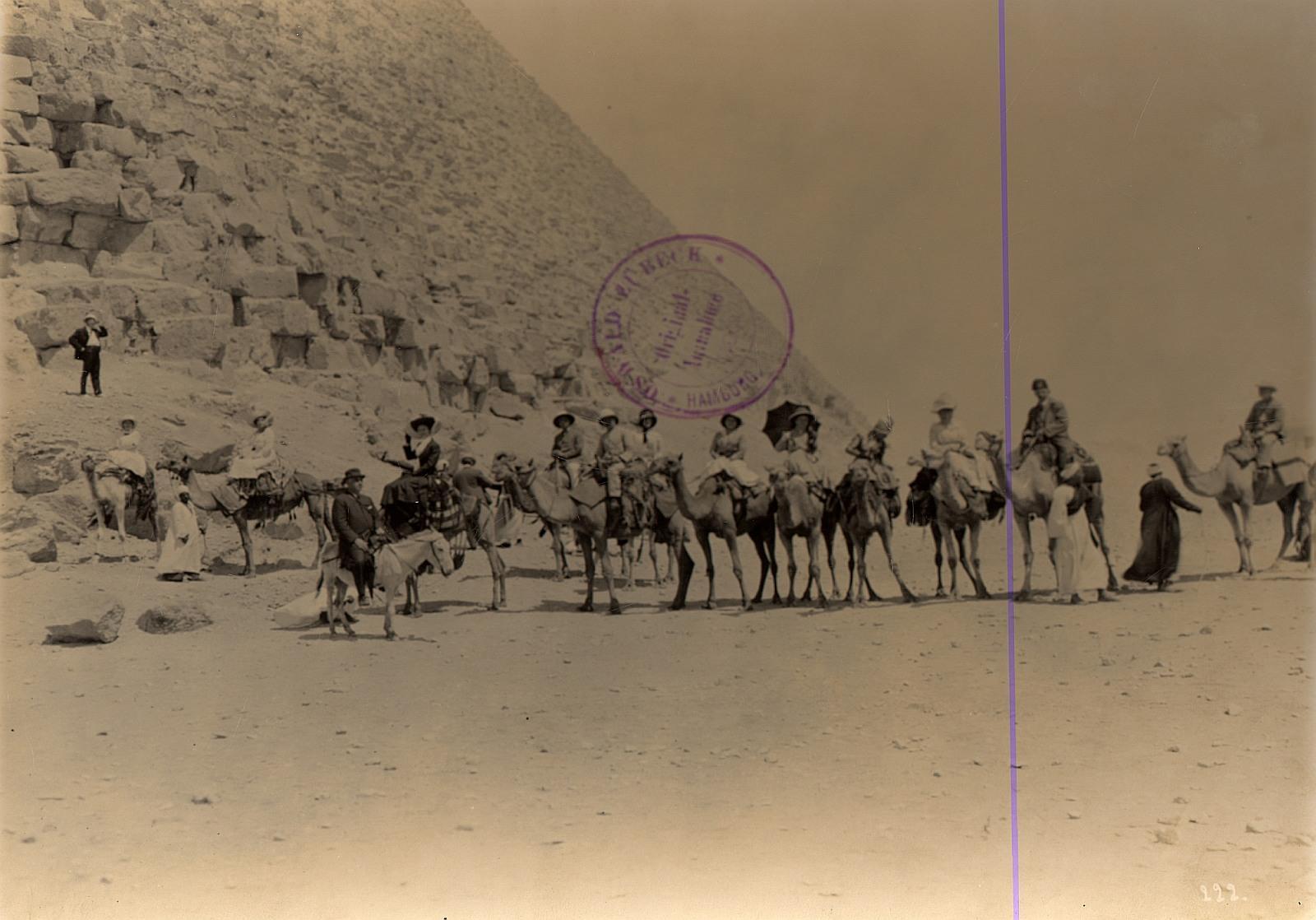 Гиза. Туристическая группа на верблюдах и ослах с туристическими гидами у подножия пирамиды