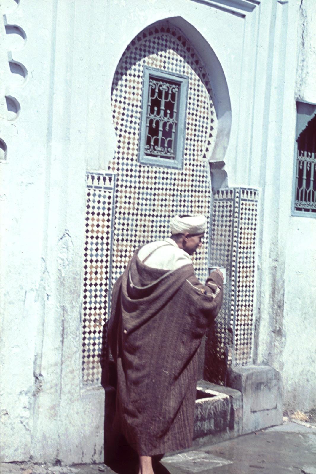 Человек, пьющий воду из украшенного мозаикой фонтана