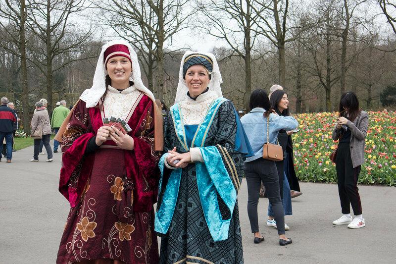 Girls in national costumes posing in a botanical garden of Keukenhof in spring