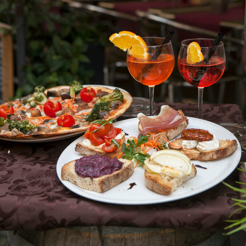 the Wine in glasses, plates with pizza and sandwiches with jamon and cheese on the table at the entrance to the restaurant