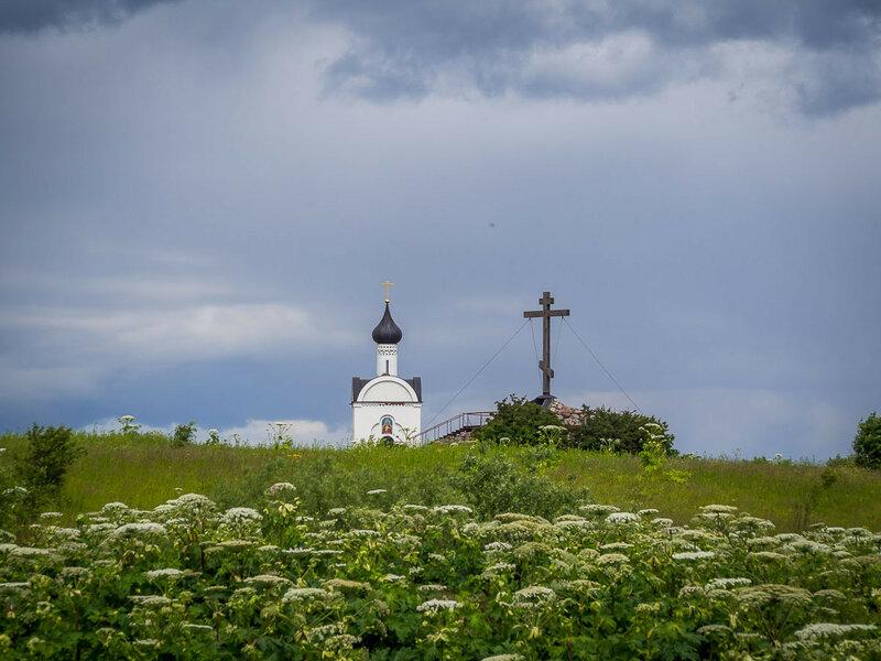 За деревней виднеются поклонный крест и часовня Державной Богоматери.