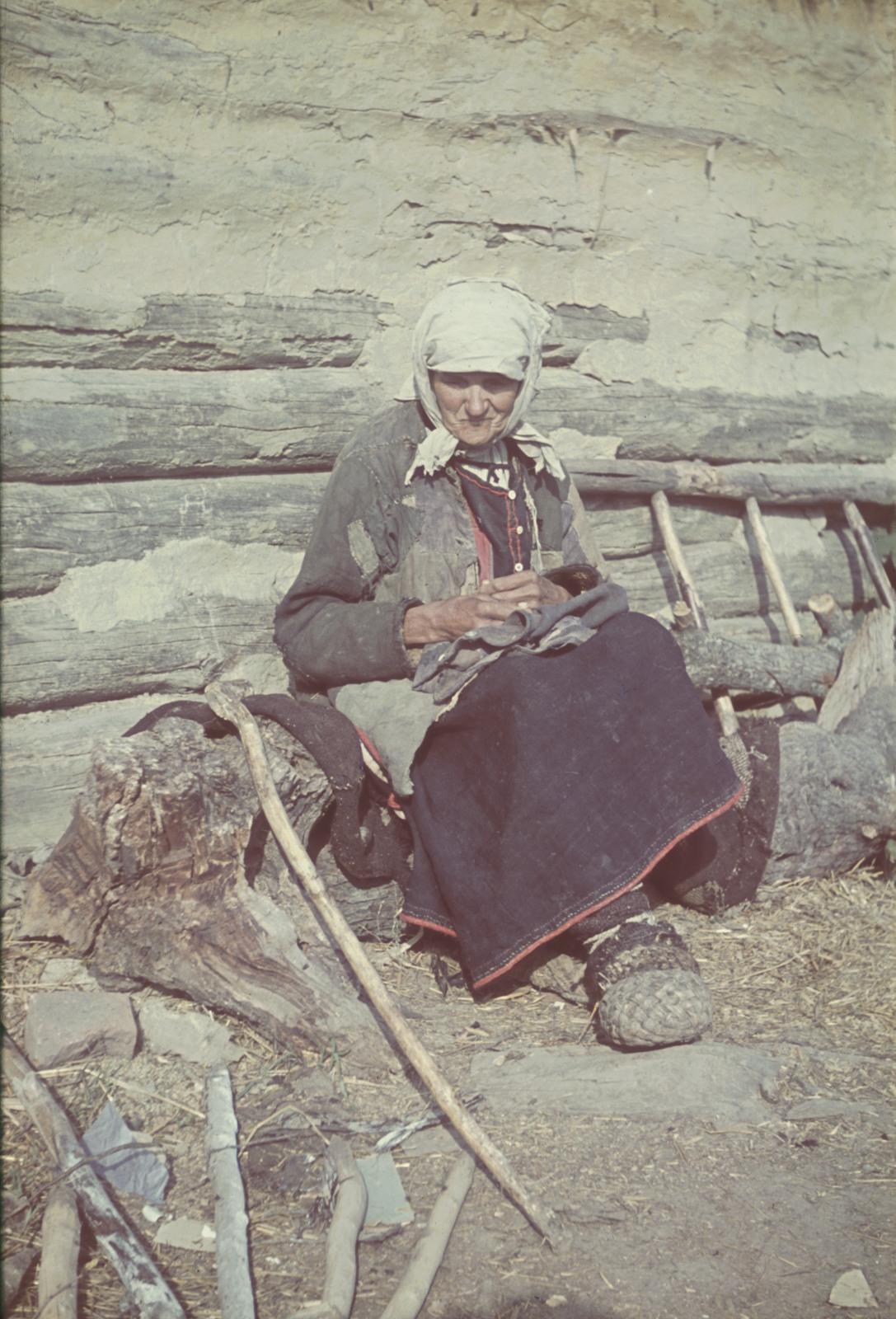 Старуха, сидящая возле дома