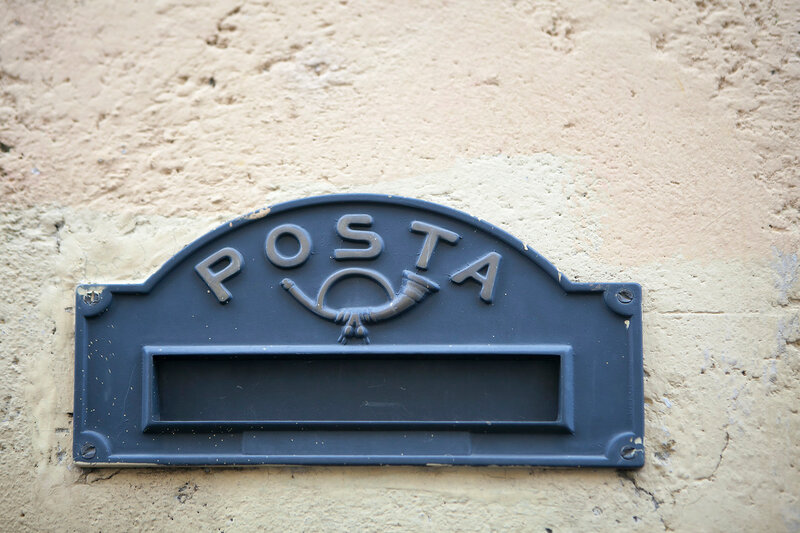 the Old Italian mailslot with traditional symbol of trumpett and message Posta - Mail.