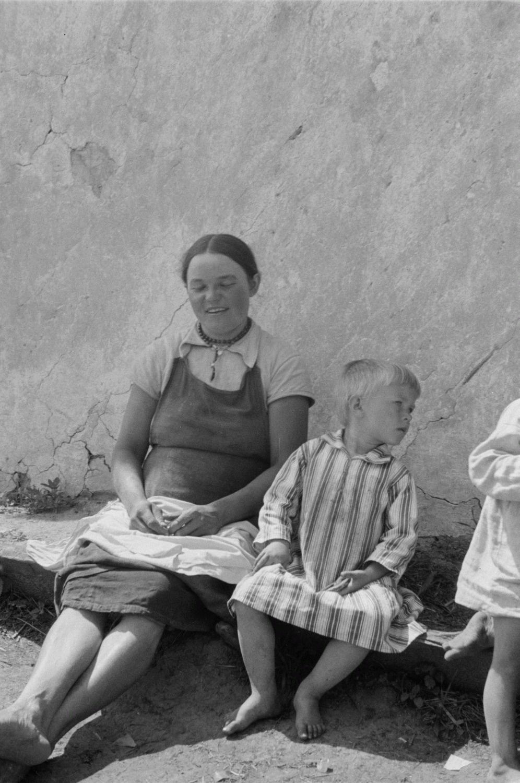 Молодая женщина с маленьким мальчиком на скамейке перед домом