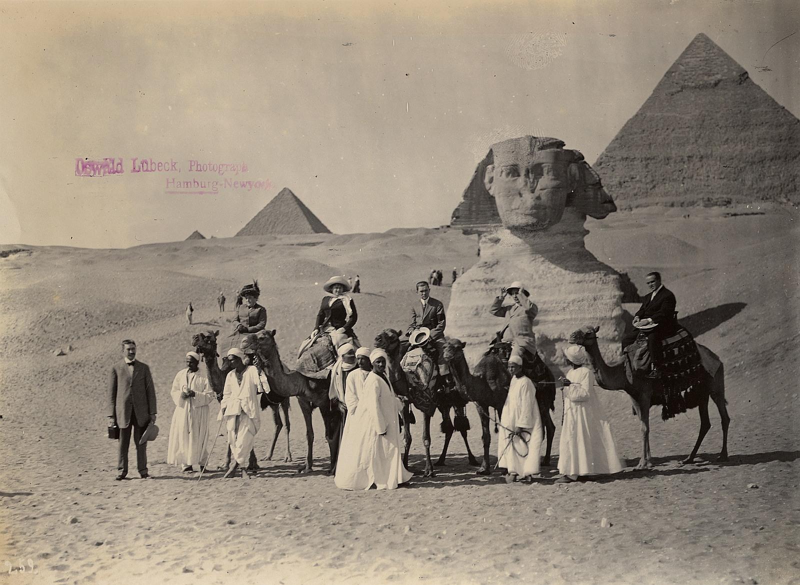 Гиза. Туристы на верблюдах позируют с местными гидами перед Сфинксом и пирамидами