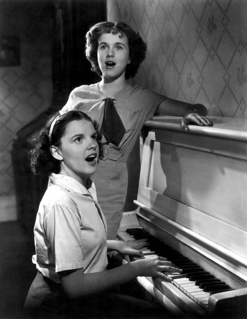 circa 1936: Judy Garland and Deanna Durbin Singing at Piano.