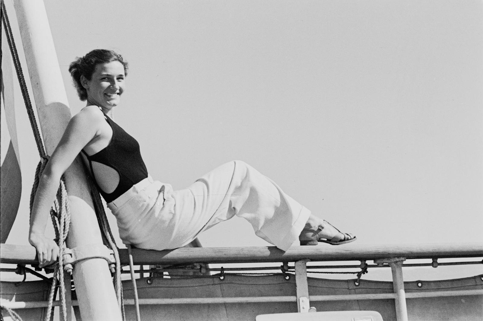 Молодая женщина, сидящая на перилах