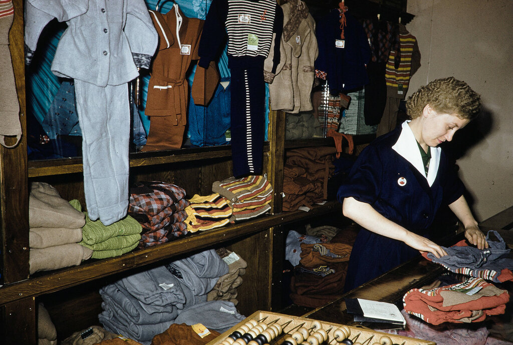 Russia, clerk folding clothes for display at store in Moscow