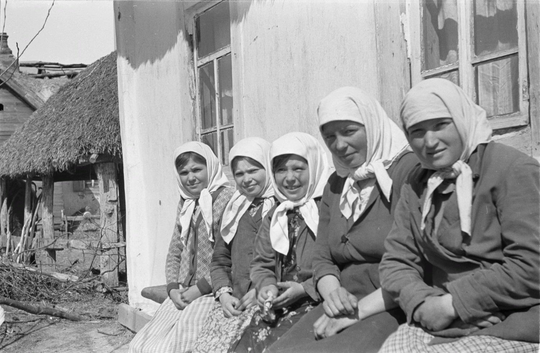 Женщины и девочки на скамейке перед домом
