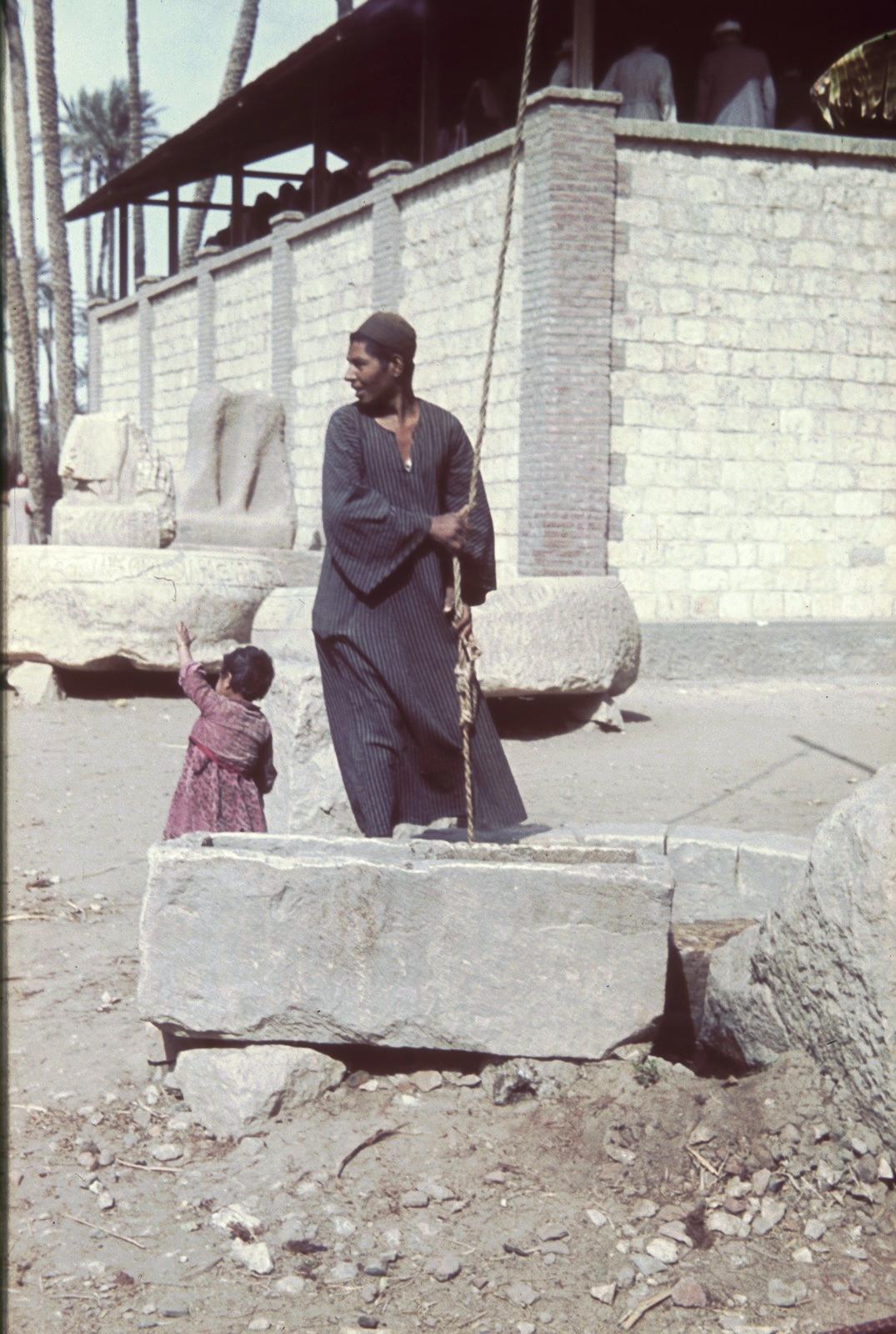 Мужчина с ребенком у колодца
