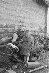 Старушка с маленьким мальчиком возле дома
