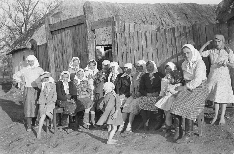 Группа сельских жителей с детьми перед входом во двор