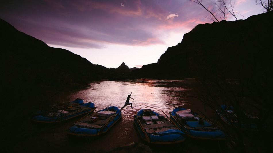 3. Один из членов команды прыгает по лодкам в поисках еды и холодного пива во время ночного привала.