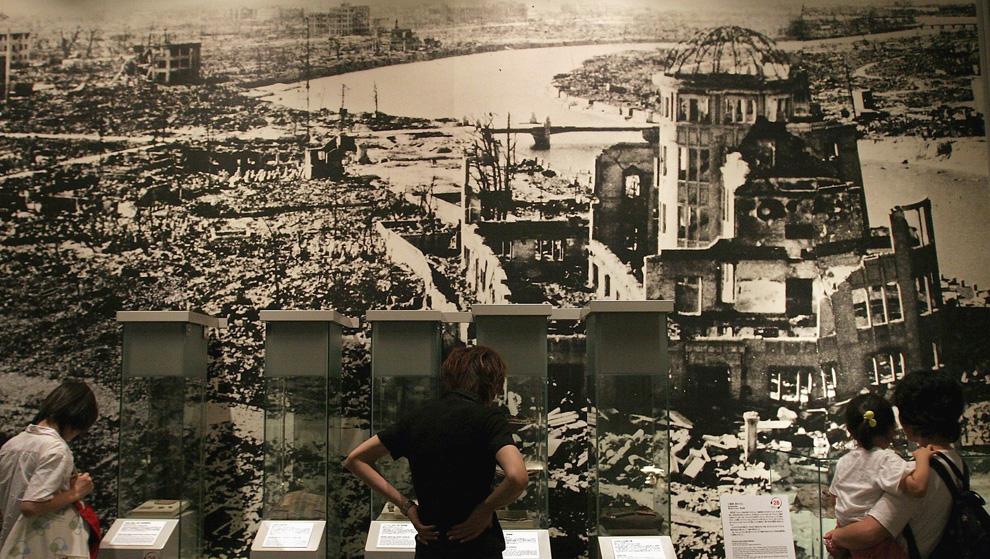 32. Посетители мемориального парка Хиросимы смотрят на панорамный вид последствий атомного взрыва, 2