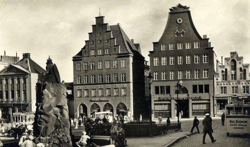 Flensburgs Südermarkt Anfang der 1930er Jahre mit der Rückseite des Bismarckbrunnens, mit spielenden Kindern im Brunnenbecken