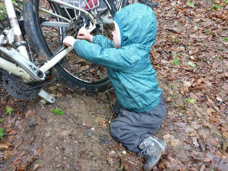 ребенок играет с велосипедом в походе