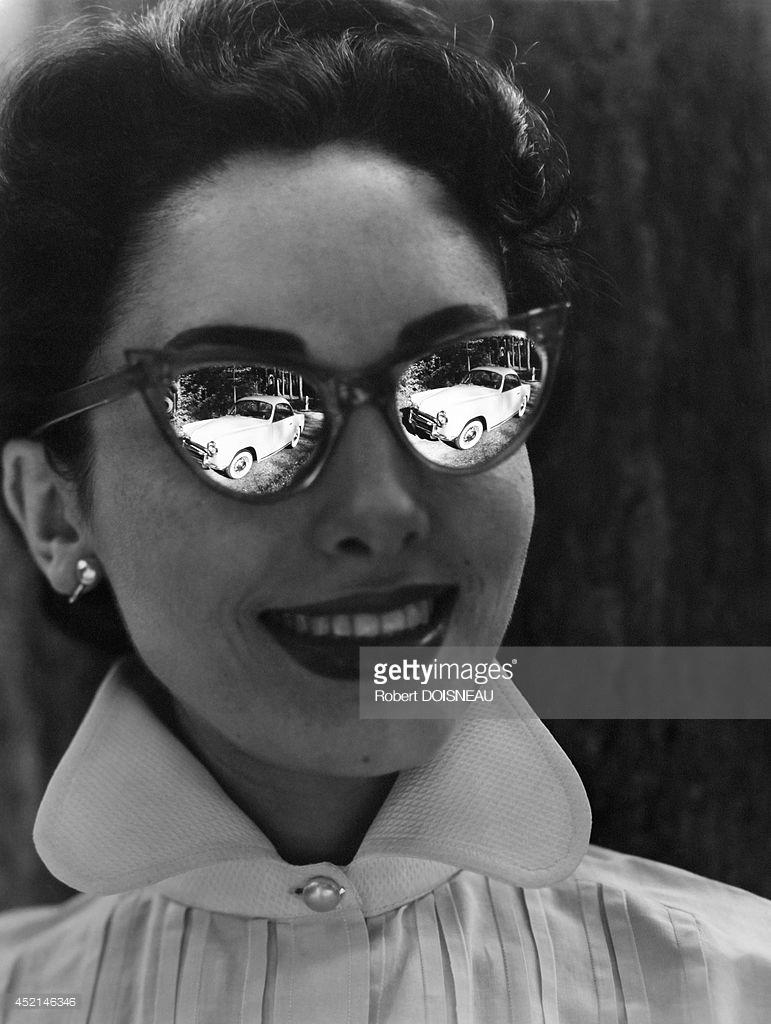 1953. Автомобиль отражается в очках молодой женщины