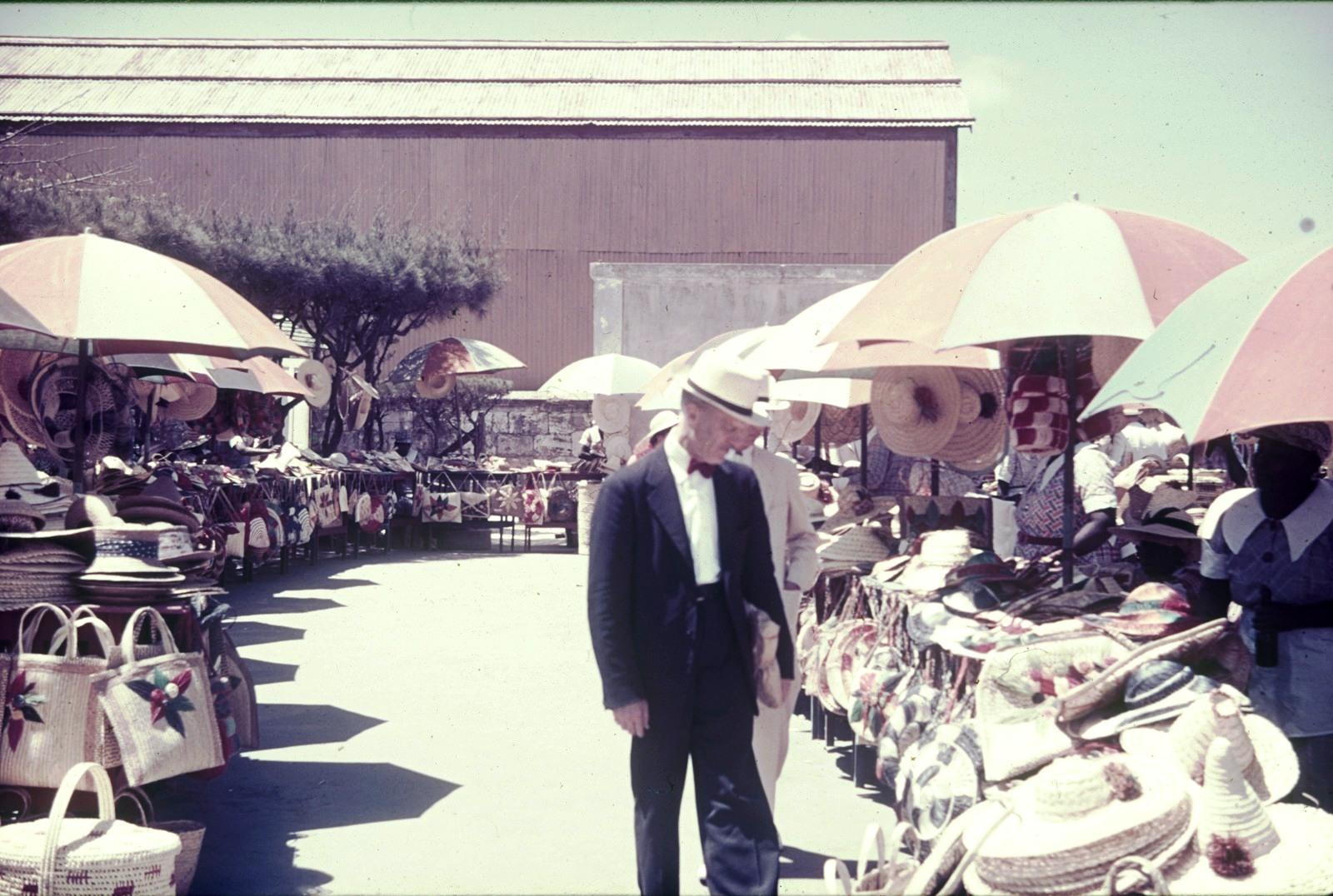 Рио-де-Жанейро.Турист на рынке возле торговых рядов с соломенными шляпами и сумочками