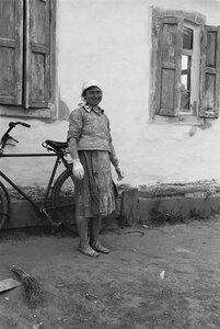 Крестьянка с велосипедом перед крестьянским домом