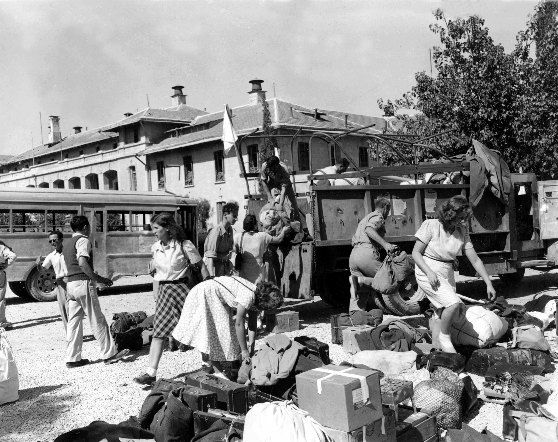 Еврейские медсестры сортируют свой багаж после безопасного возвращения в Иерусалим в бронированных автобусах конвоя Организации Объединенных Наций 8 октября
