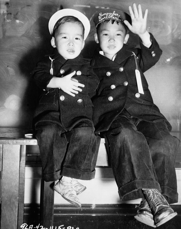 Мальчики из Сан-Франциско машут на прощание в ожидании автобусов в лагеря. На одном из них шапочка с