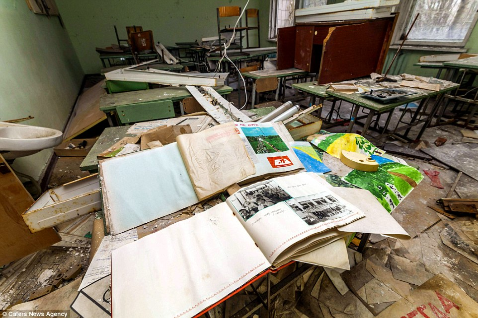 Альбомы для рисования и незавершенные рисунки разбросаны по школьному классу вместе со сломанной меб