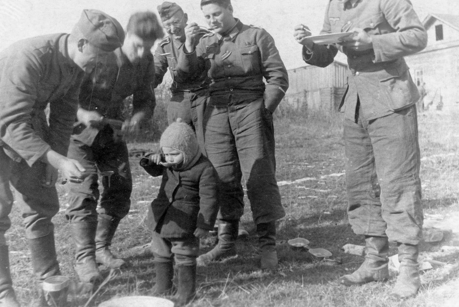 Ребенок в окружении немецких солдат.
