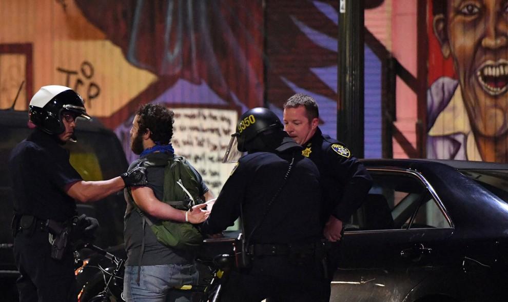 Полиция арестовывает демонстранта на акции протеста против Дональда Трампа в Окленде, штат Калифорни