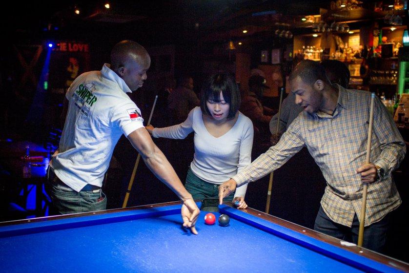 Кьёнг-ок играет в бильярд с Кристианом Кингом из Либерии (слева) и Джерри Александером из Канады в я