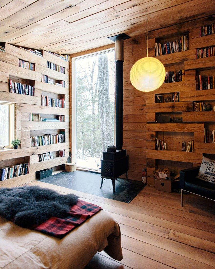 Свободное пространство между дубовыми брёвнами образует книжные полки
