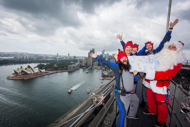 Санта-Клаус и его помощники эльфы на вершине моста Харбор-Бридж, Сидней.