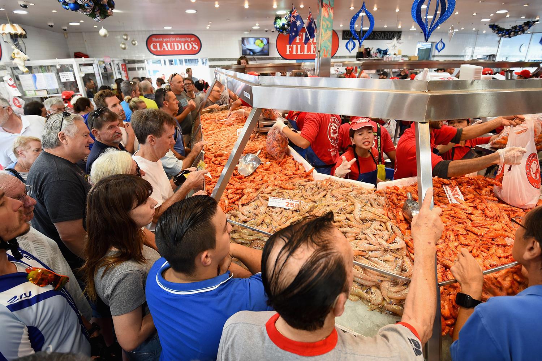 Активные предпраздничные закупки на рыбном рынке в Сиднее, который работает 36 часов подряд с 5 утра 23 декабря до 5 вечера 24 декабря (канун католического Рождества).