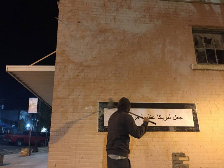 An artist trolls the xenophobes by displaying the Trump's slogan in Arabic