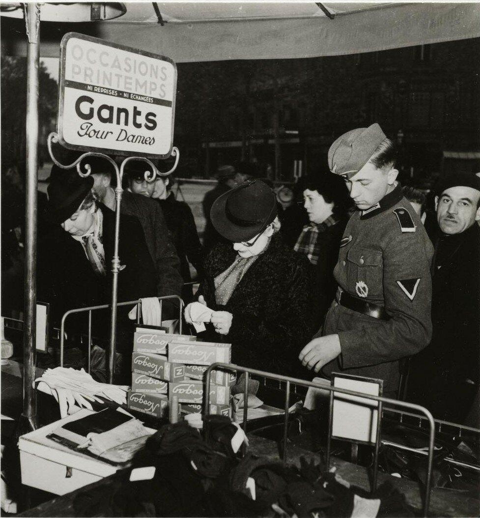 Немецкий солдат и женщина в отделе дамских перчаток универмага «Прентам»