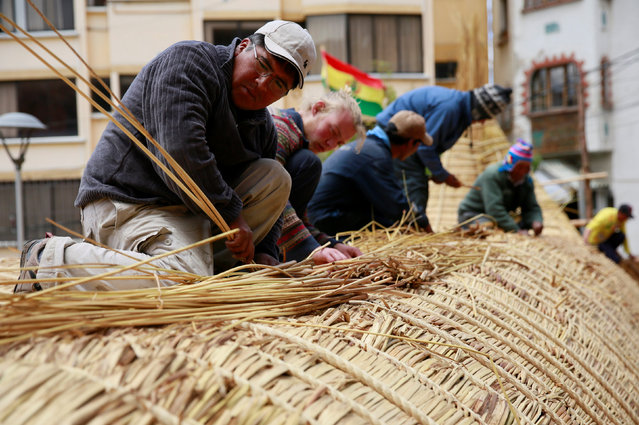 "Builders work on top of the ""Viracocha III"", a boat made only from the totora reed, as it is being p"