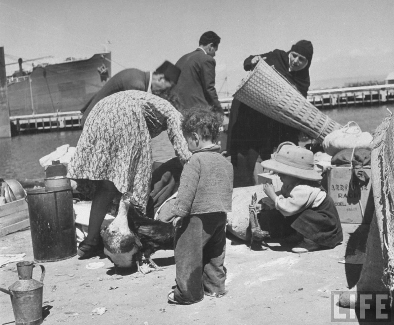 Беженцы собирают свои вещи, чтобы взойти на борт британского корабля. Хайфа. Апрель