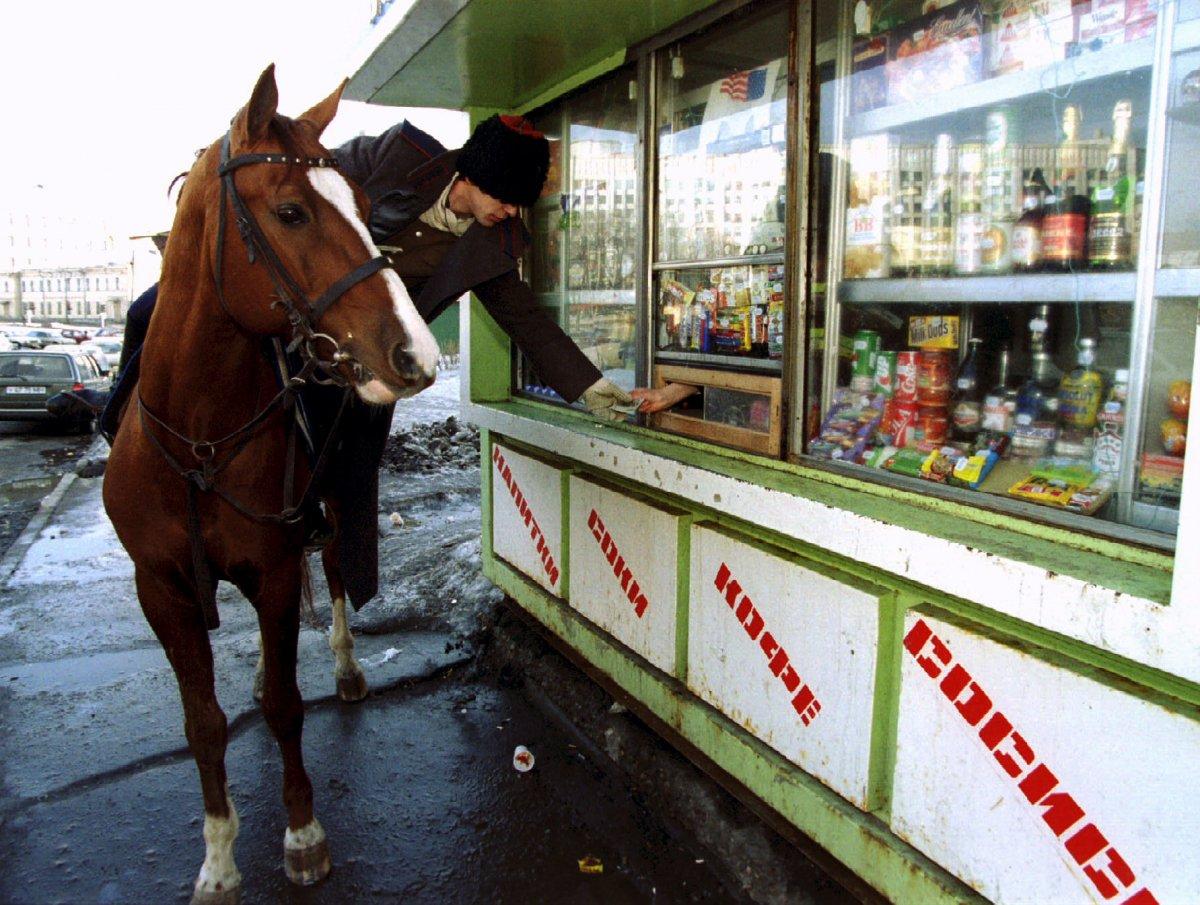 Казак на лошади покупает водку в киоске во время парада в честь Дня святого Патрика в Москве. Меропр
