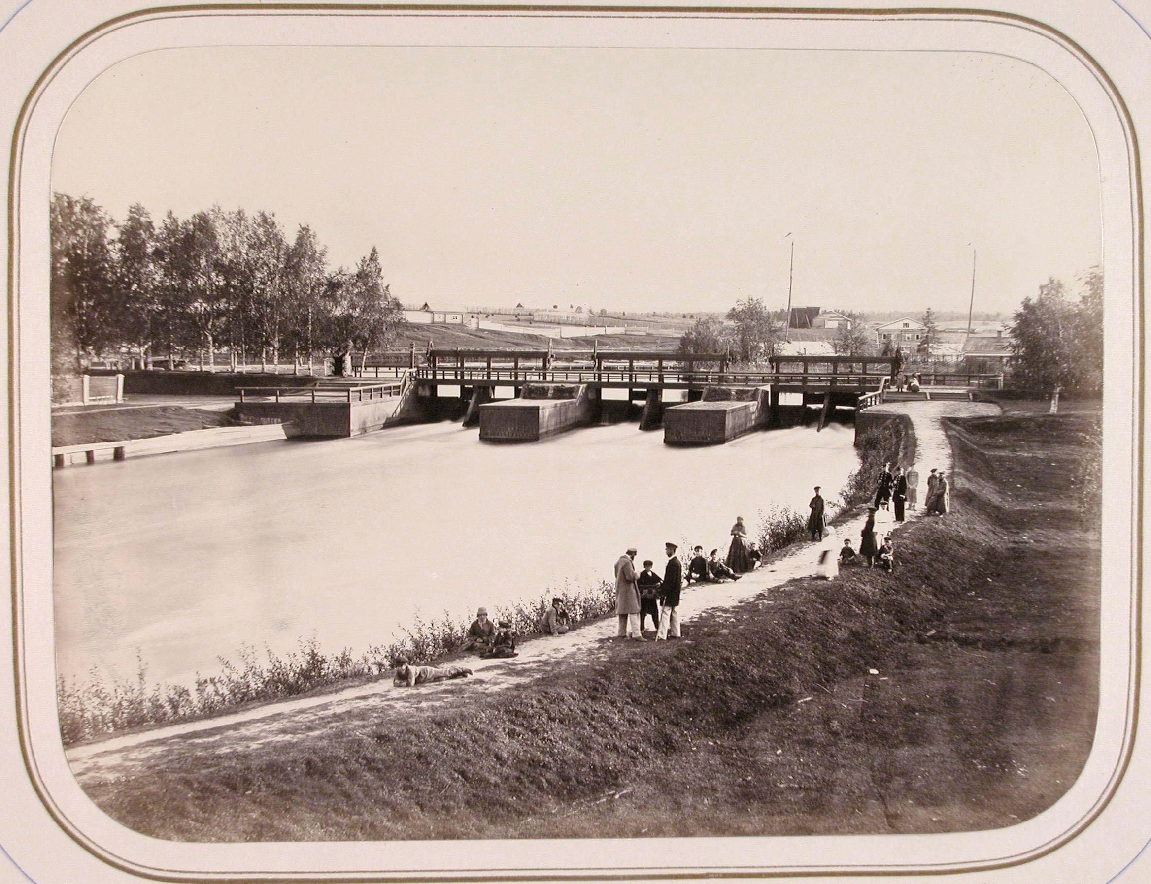 Местные жители на набережной; в центре - плотина Св. Сергия
