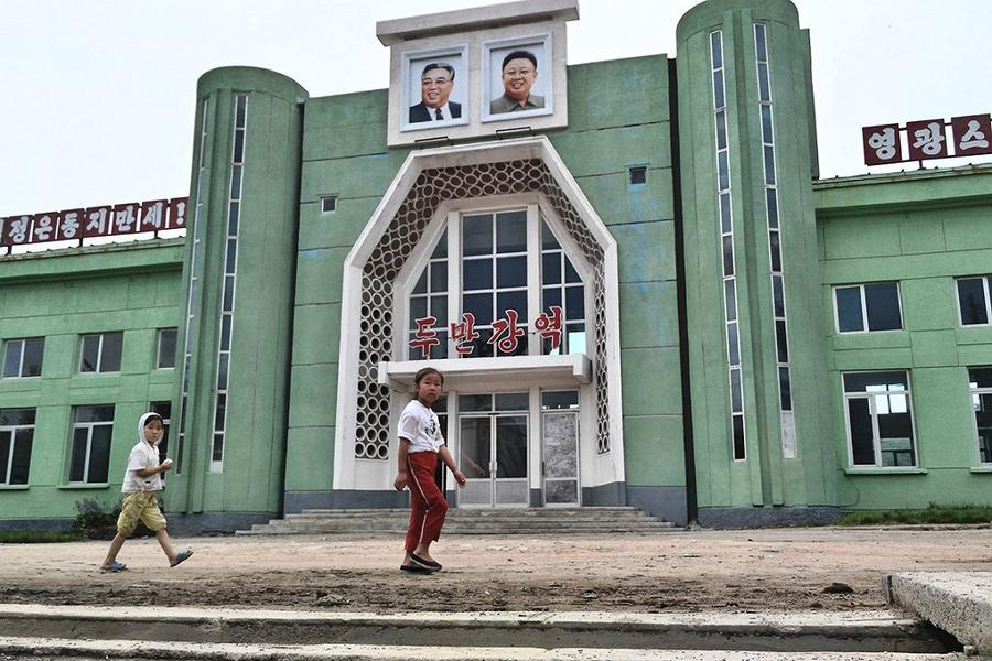 14. Дети проходят мимо железнодорожного вокзала в Туманганге