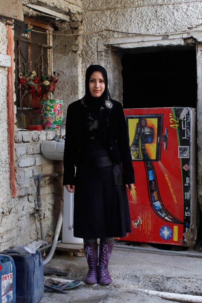 34. 18-летняя Роауа Мансур, мать, позирует у своего дома в Багдаде. На вопрос