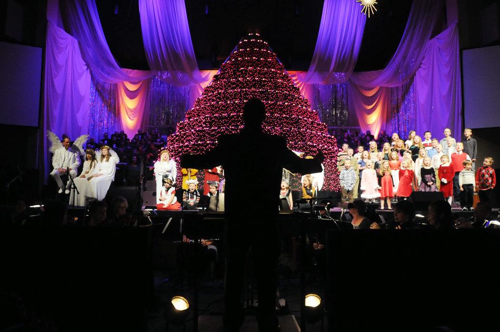 31. Дирижер с хором и оркестром на рождественском концерте в Нампе, штат Айдахо. Здание в несколько
