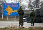 Russian servicemen stand on duty near a map of the Crimea region near the city of Kerch