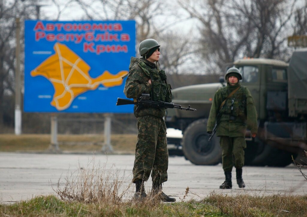 Russian servicemen stand on duty near a map of the Crimea region near the city of Kerch
