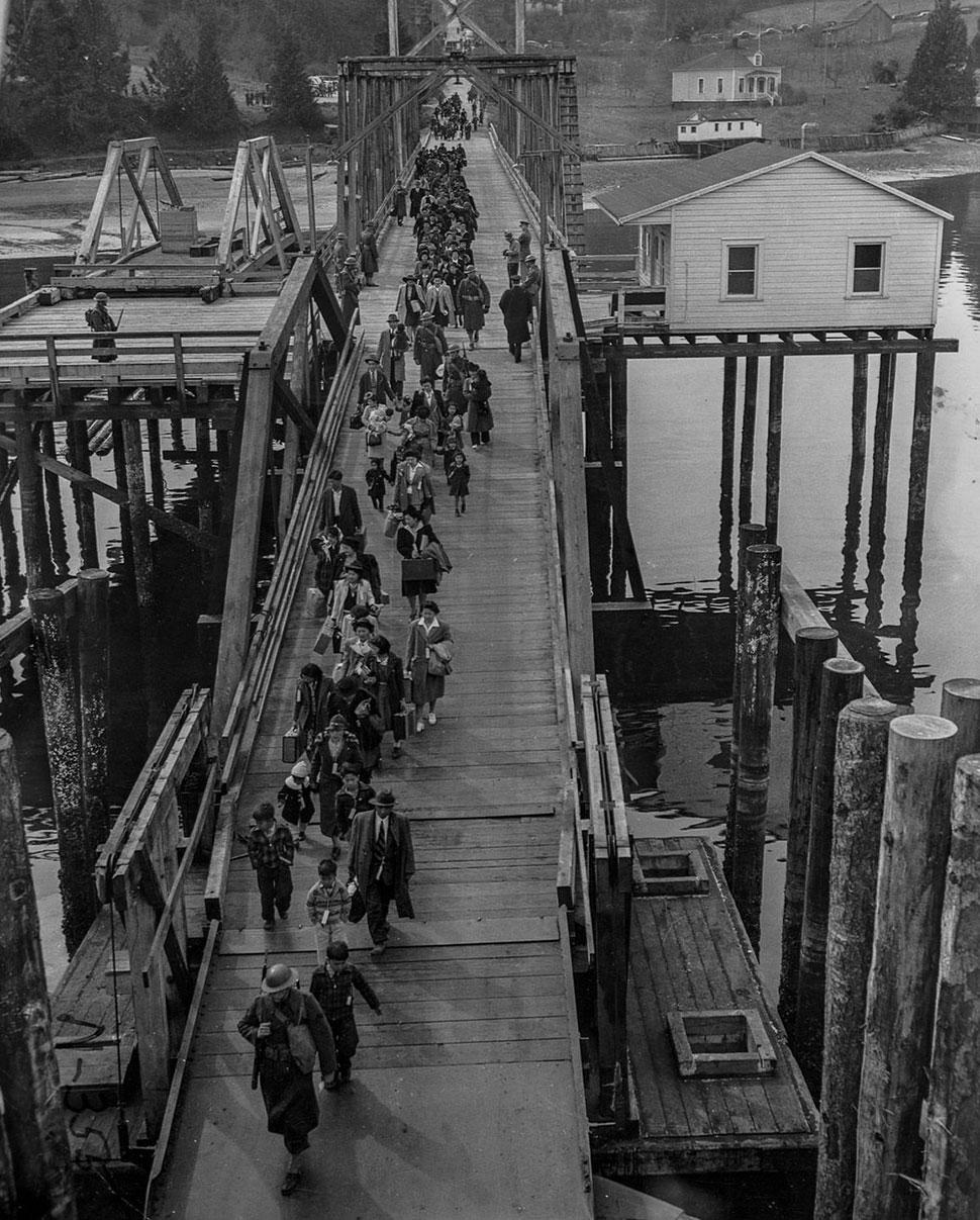 Американцы японского происхождения и сопровождающие их солдаты идут через мост на острове Бейнбридж,