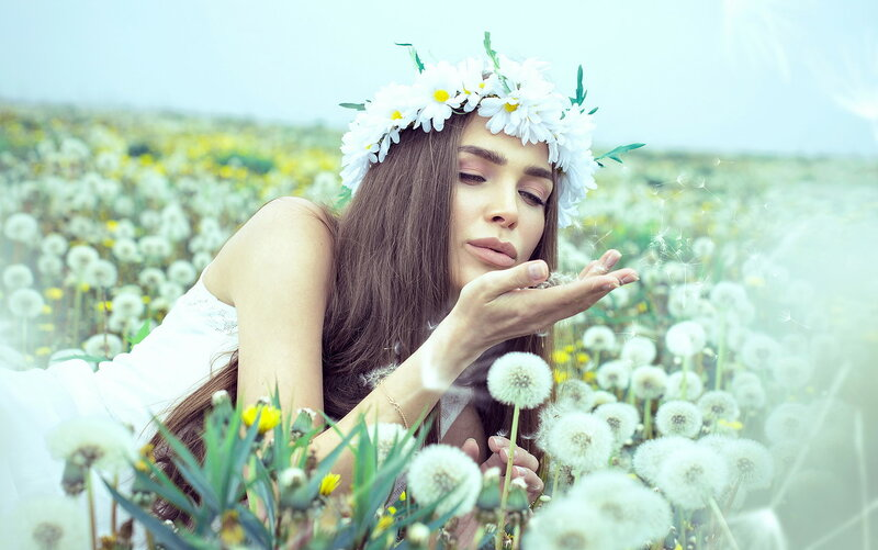Young woman blowing dandelions