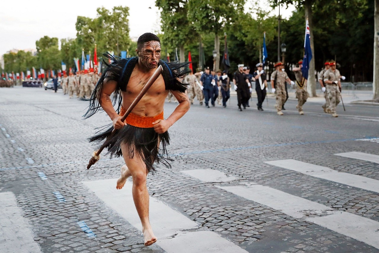 Воин Майори (Новая Зеландия) бежит вдоль Елисейских полей в Париже, в то время как солдаты Новой Зеландии тоже репетируют к дню Бастилии, Париж (12 июля 2016).jpg