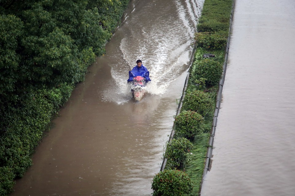 A rider drives past a flooded street in Changzhou