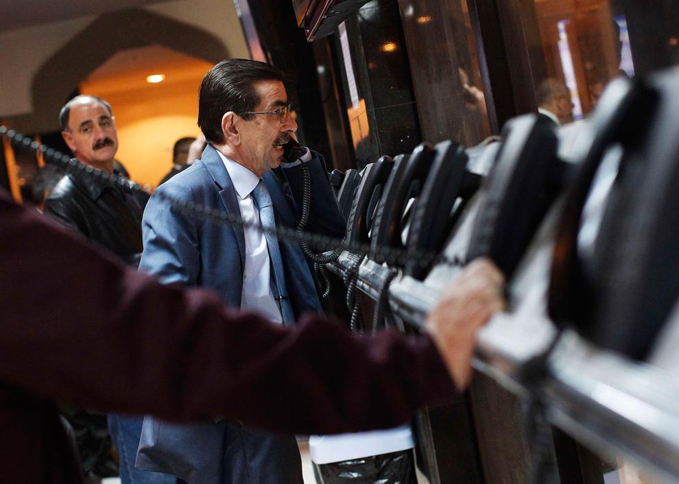 8. Инвесторы на телефонах на Иракской фондовой бирже в Багдаде. Биржа начала работать в июне 2004 го
